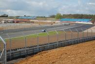A Sainteloc Audi heads down Farm Straight with the construction sight of the new 'Wing' pits in the