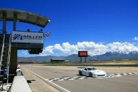 A car speeds over the finish line at Miller Motorsports Park